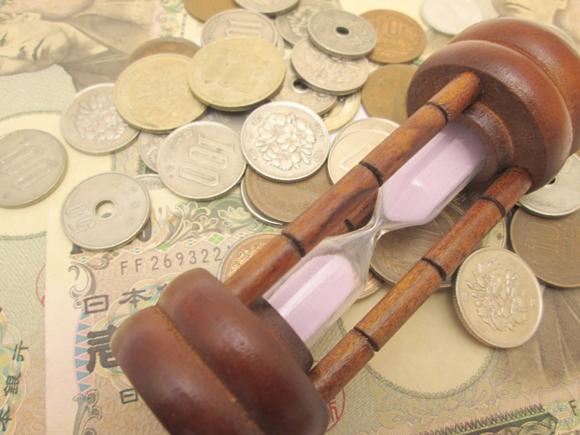 コインと砂時計の画像